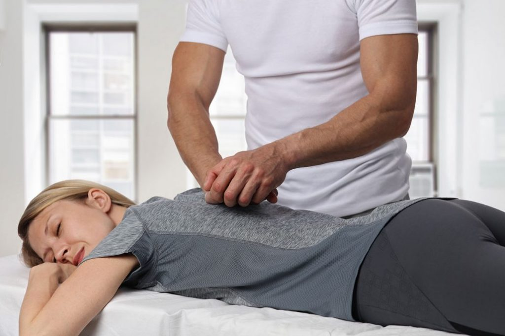 Woman having chiropractic back adjustment